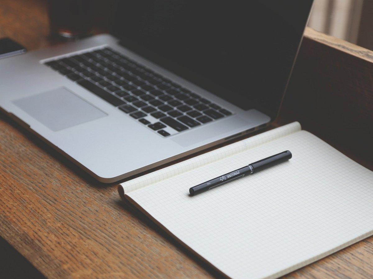 laptop-neben-notizheft
